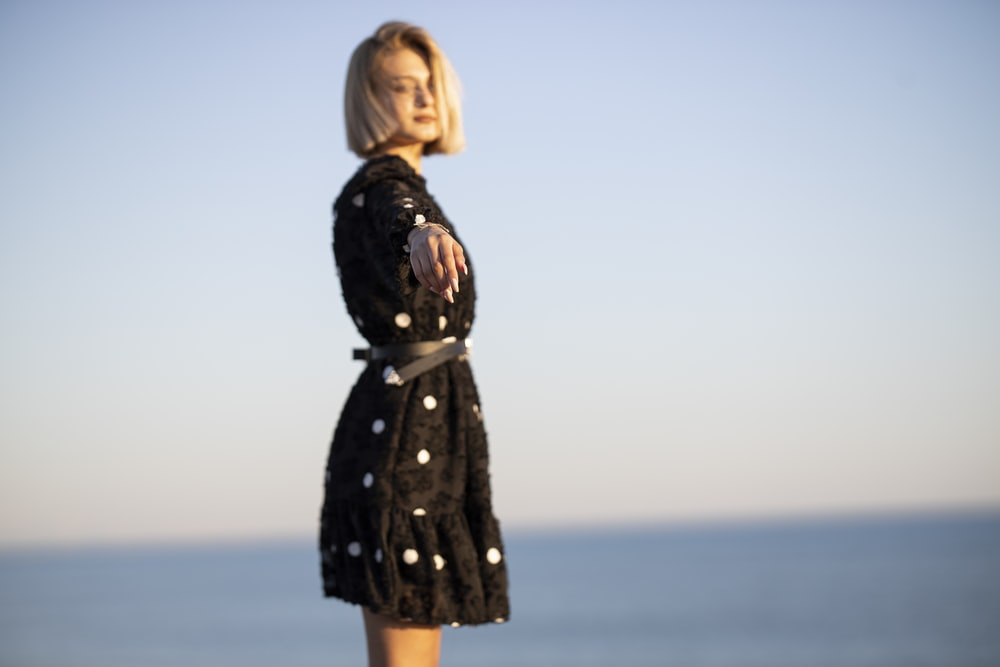 woman in black long sleeve dress standing on seashore during daytime