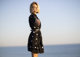 woman in black long sleeve dress standing on seashore during daytime