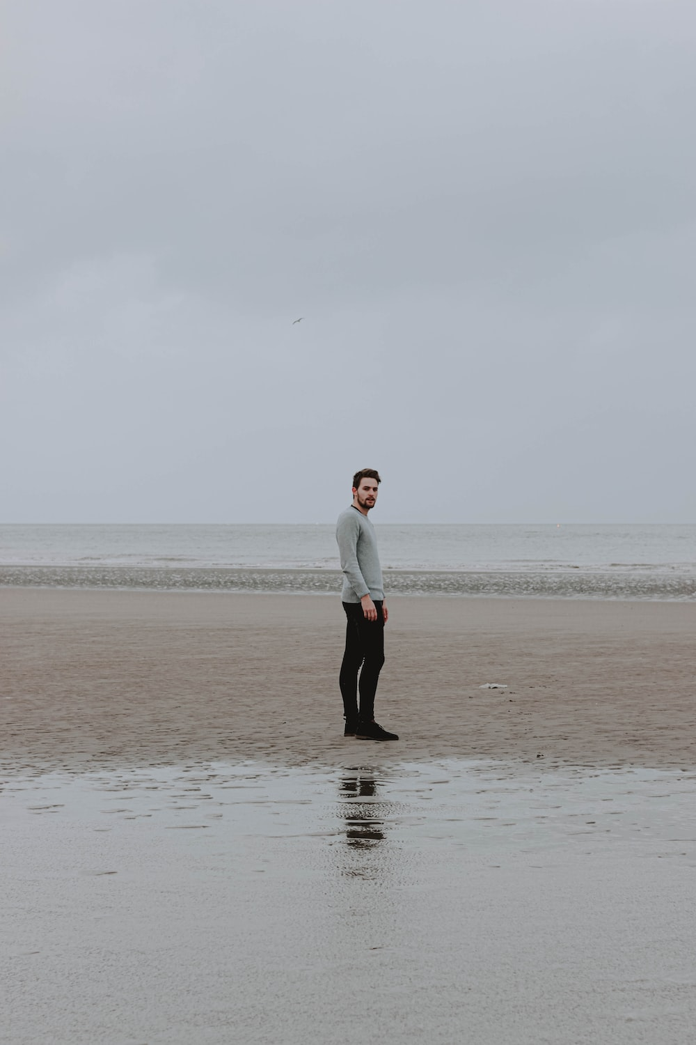 man in white dress shirt and black pants standing on seashore during daytime