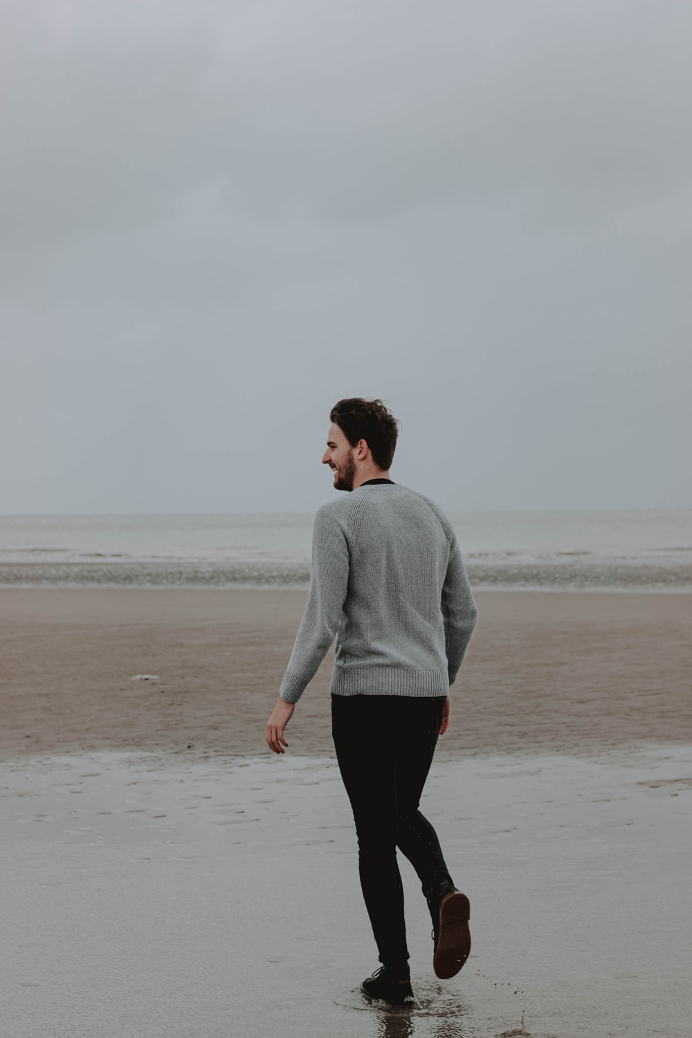 woman in gray sweater and black pants walking on beach during daytime