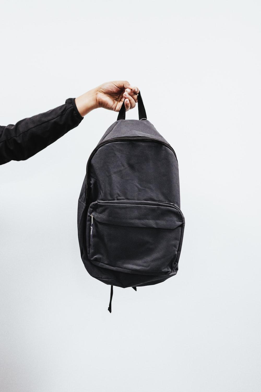 person in black jacket holding black backpack