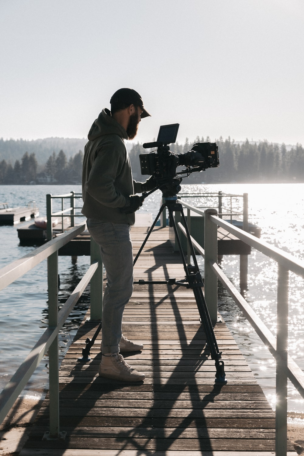 man in brown jacket and brown pants standing on dock holding camera