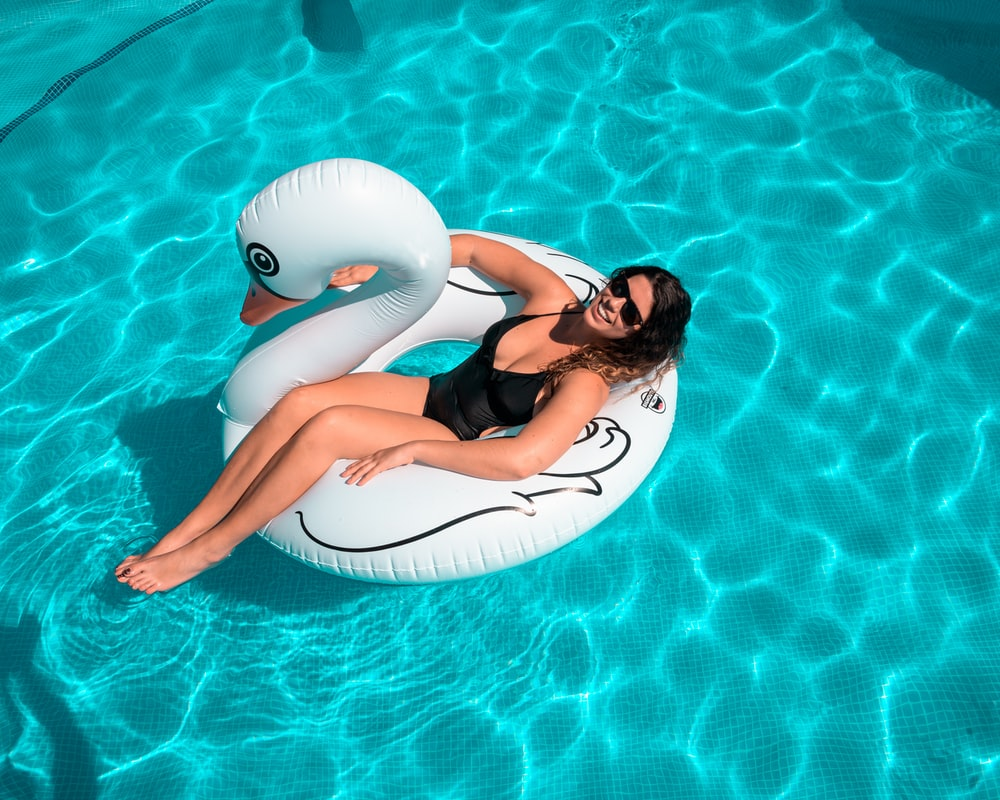 woman in black bikini lying on white surfboard on swimming pool during daytime