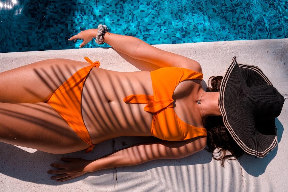 woman in orange bikini lying on white textile