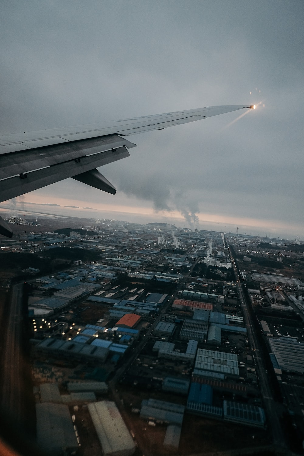 white and gray airplane wing over city during daytime