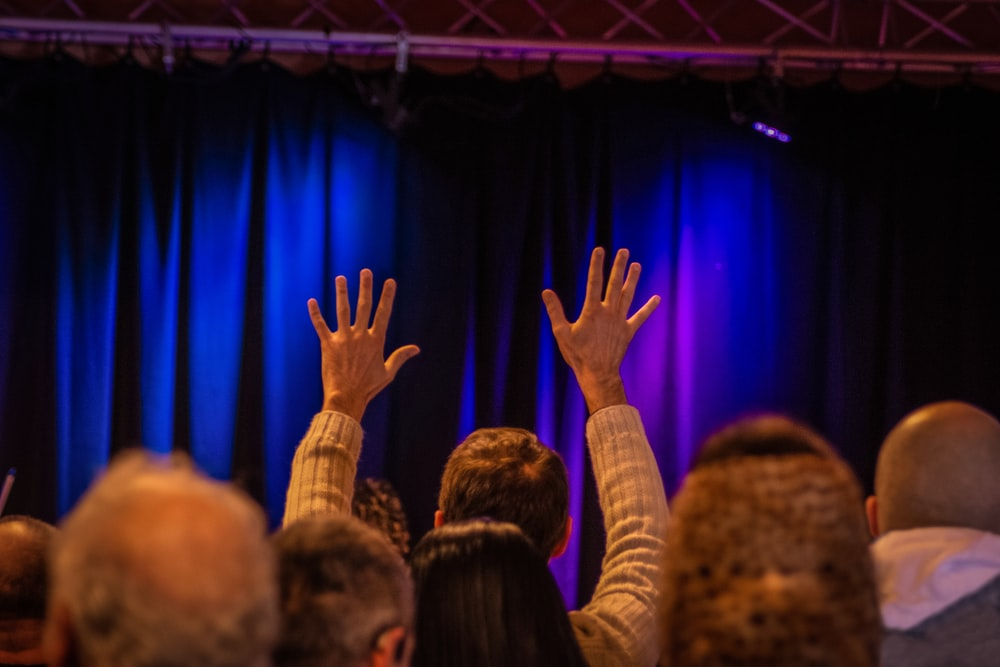 people raising their hands on the stage