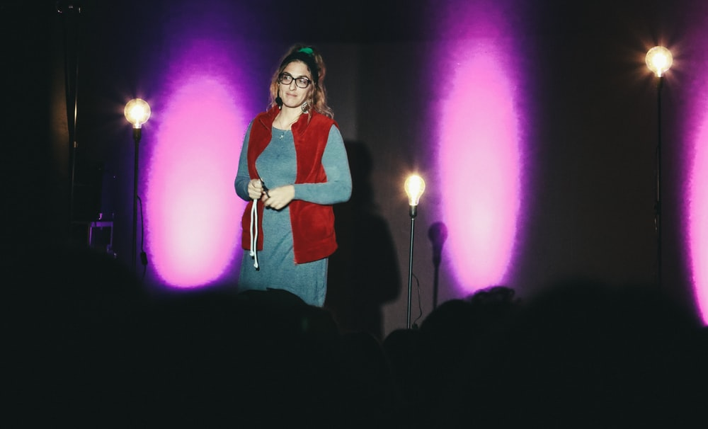 woman in red and white long sleeve shirt standing on stage