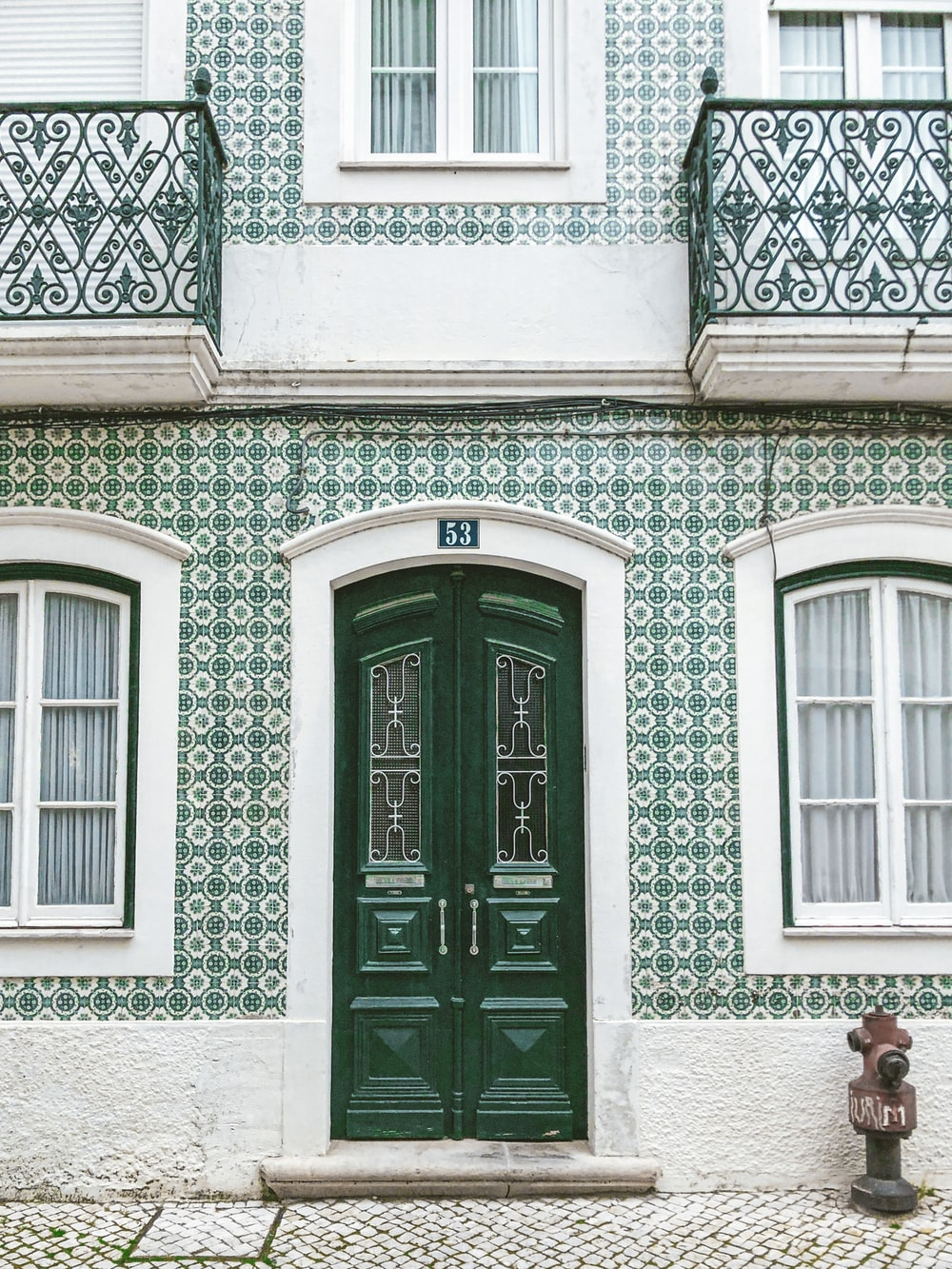 green wooden door on white concrete building