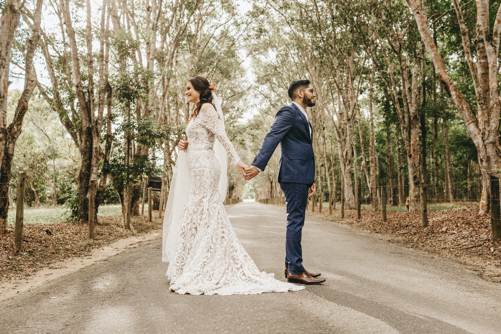 man in black suit jacket and woman in white wedding dress walking on road during daytime