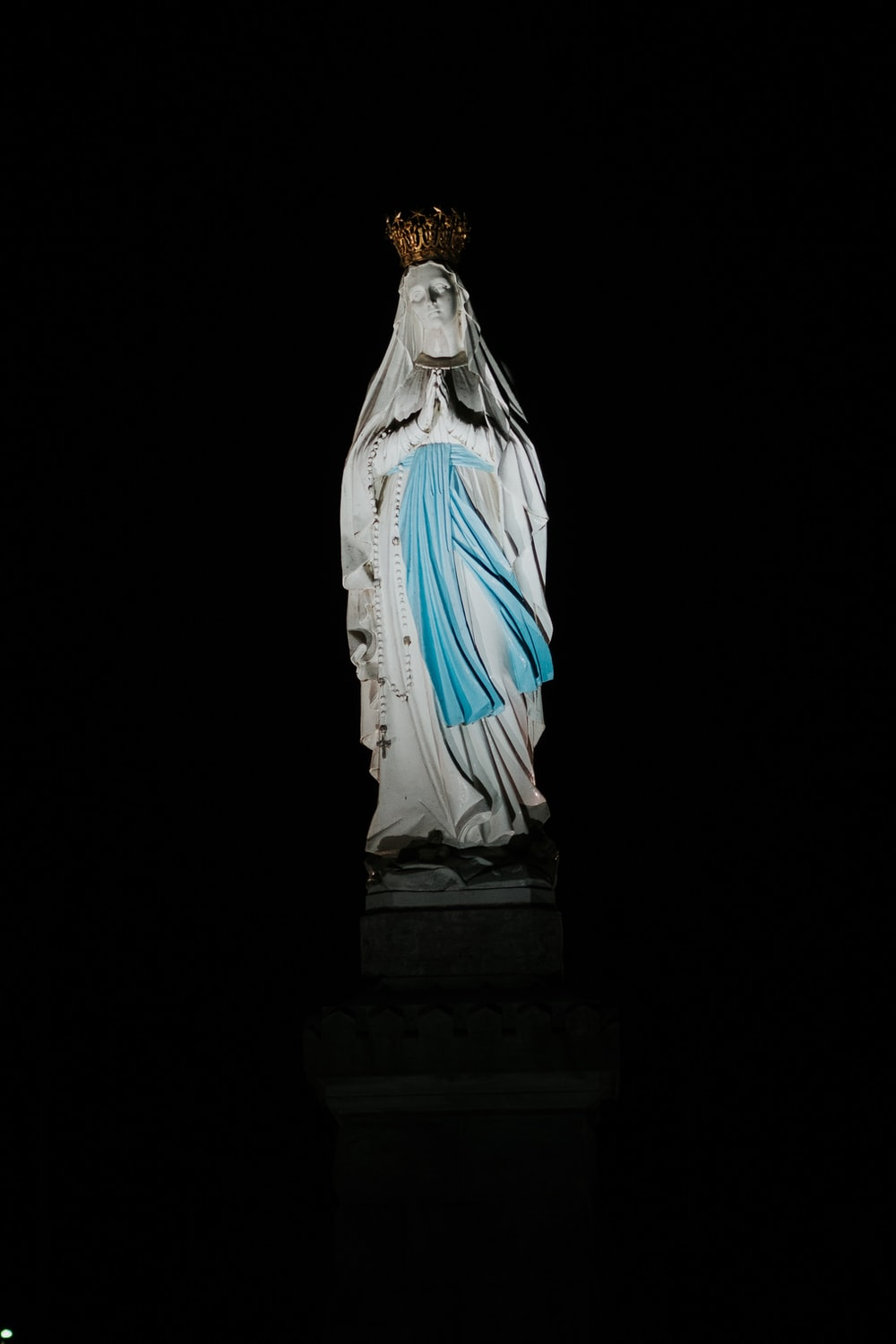 virgin mary statue on black surface