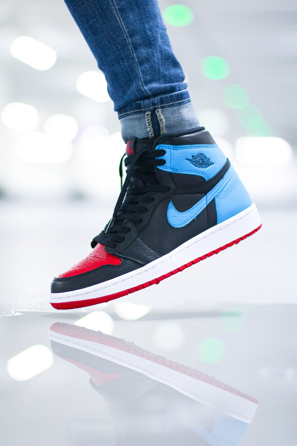 person wearing black blue and white nike air jordan 1 shoes