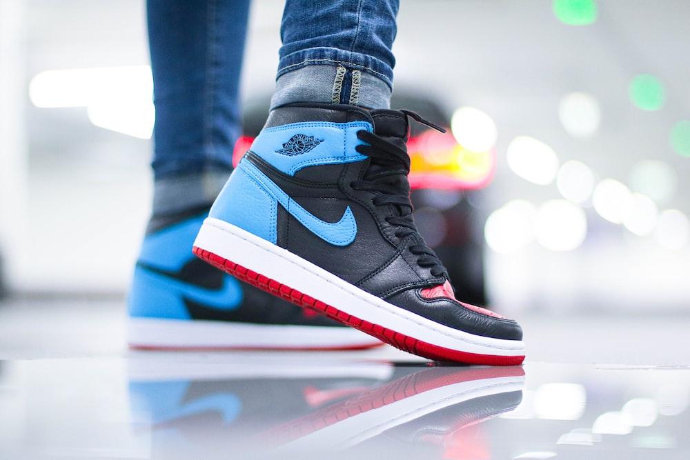 person wearing black and white nike air jordan 1 shoes