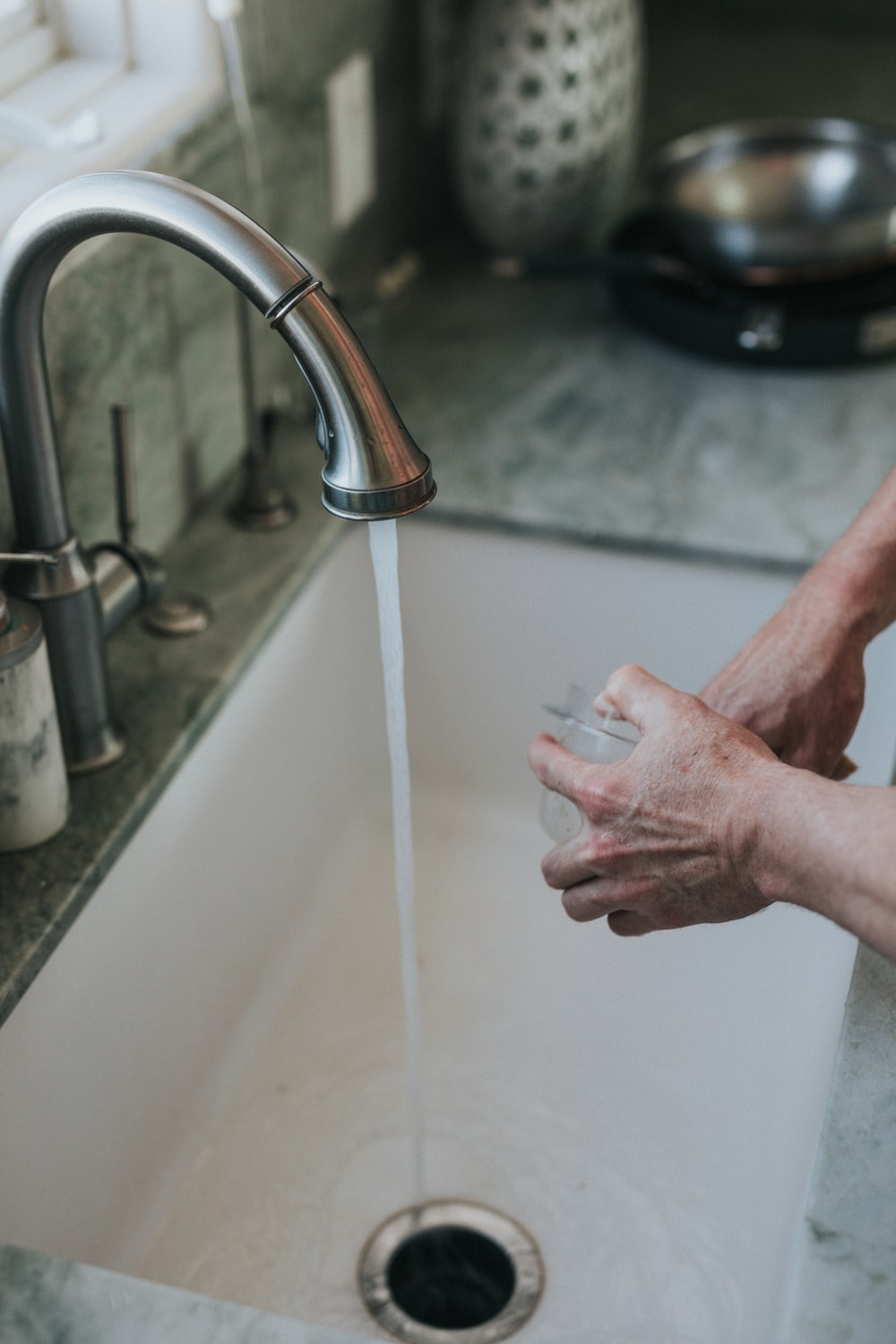 person washing hand on faucet