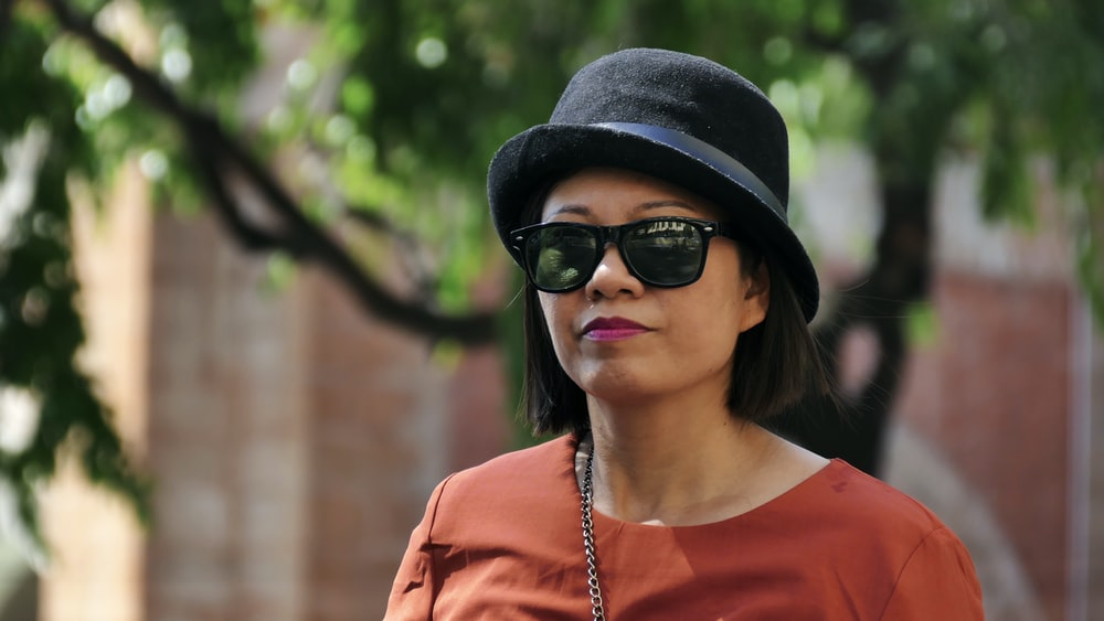 woman in orange crew neck shirt wearing black fedora hat and black sunglasses