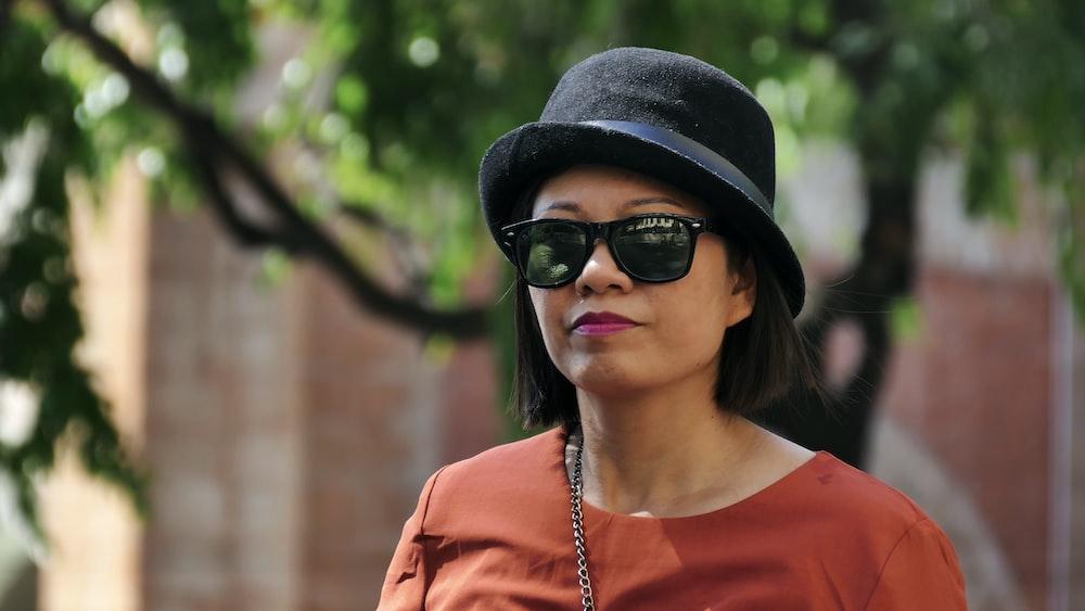 woman in orange crew neck shirt wearing black fedora hat and black sunglasses