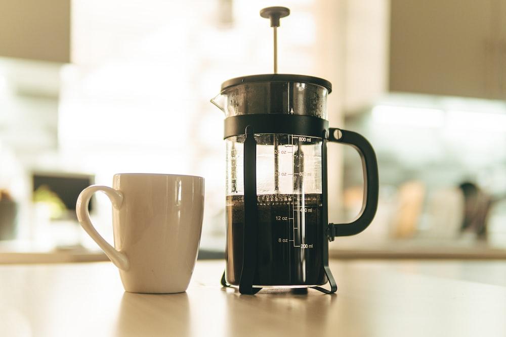 white ceramic mug beside black and white coffee mug