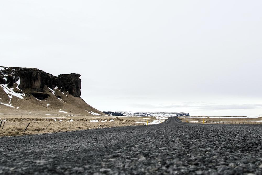 black asphalt road near brown rock formation during daytime