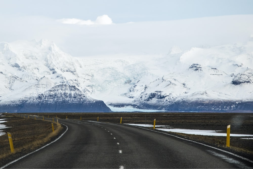 gray concrete road near snow covered mountain during daytime