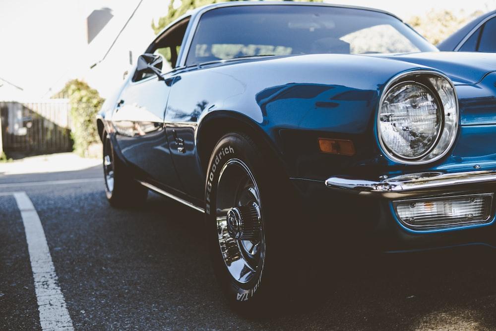 blue classic car in a parking lot