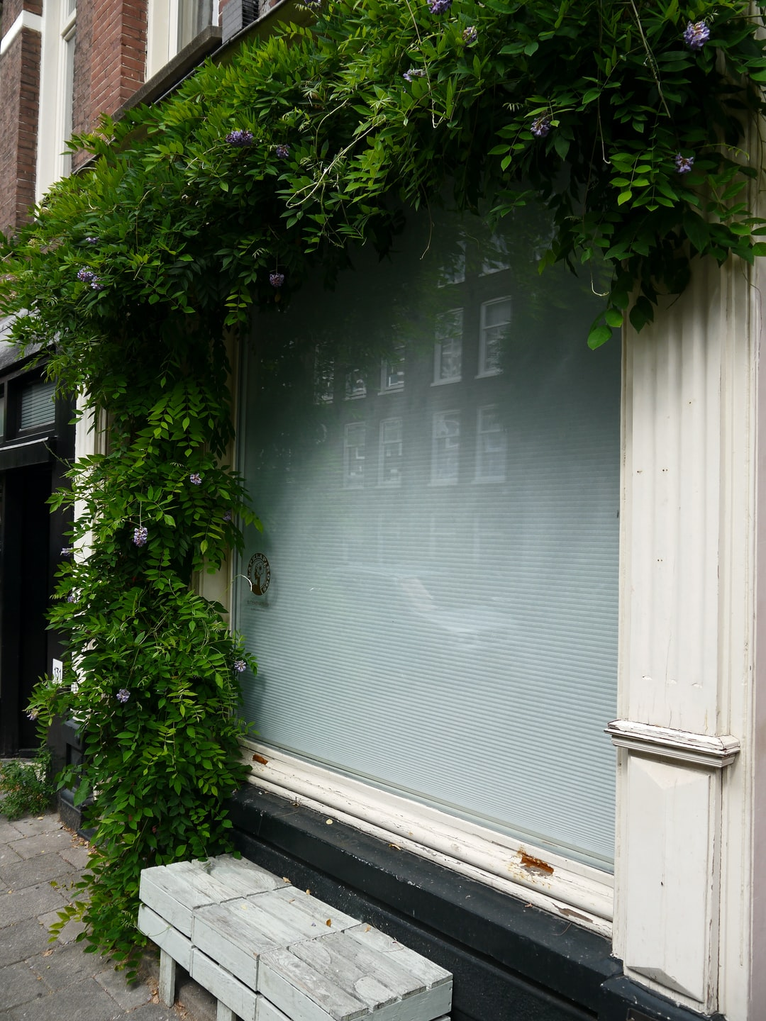 Photo of an empty reflecting shop-window with closed blinds; it is a picture in a street of the Pijp-district in Amsterdam city. Urban photography of The Netherlands by Fons Heijnsbroek