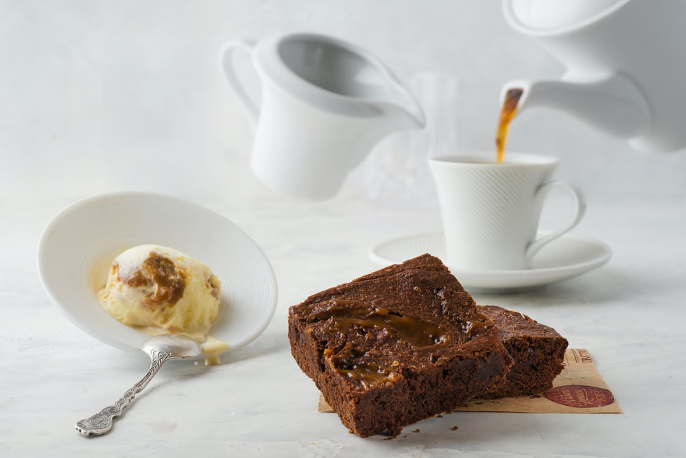 sliced chocolate cake on white ceramic plate beside stainless steel spoon