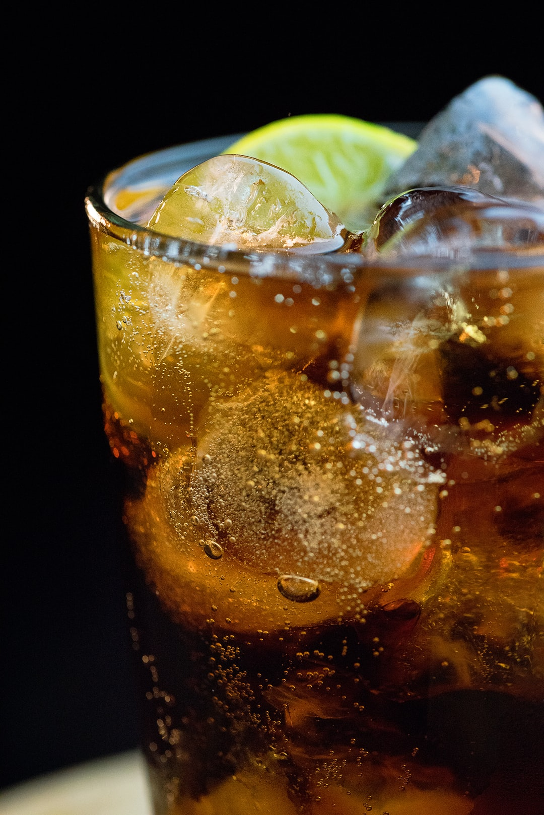 Cola with ice and lime on a dark background.