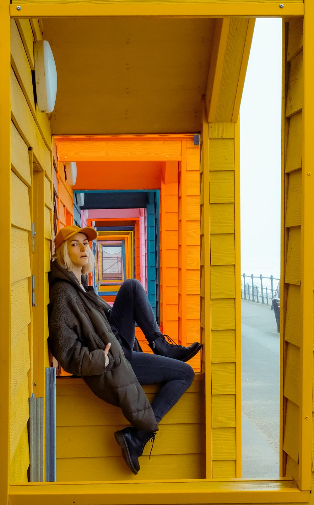 woman in brown jacket and blue denim jeans sitting on yellow wooden door during daytime