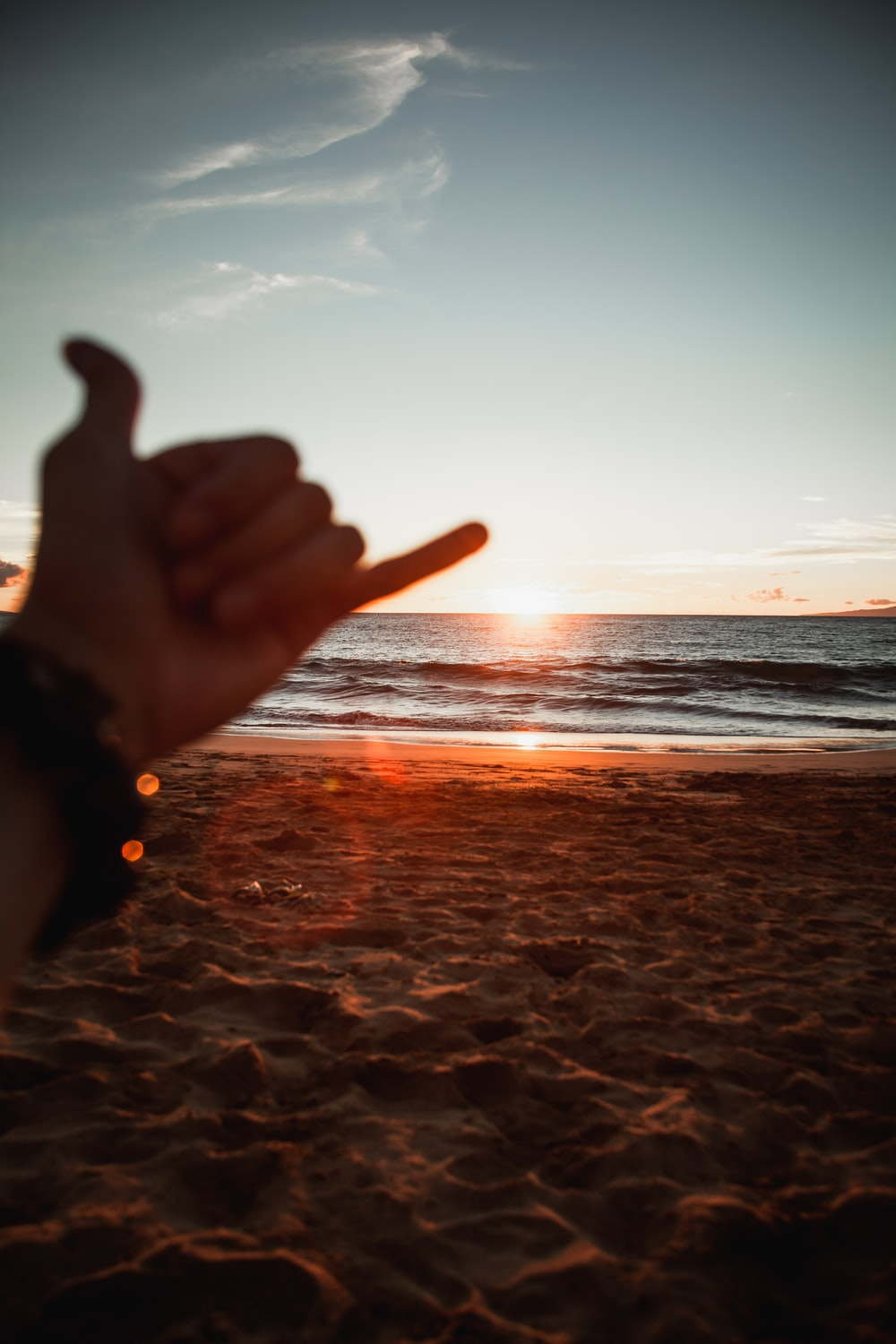 person doing peace sign near sea during sunset