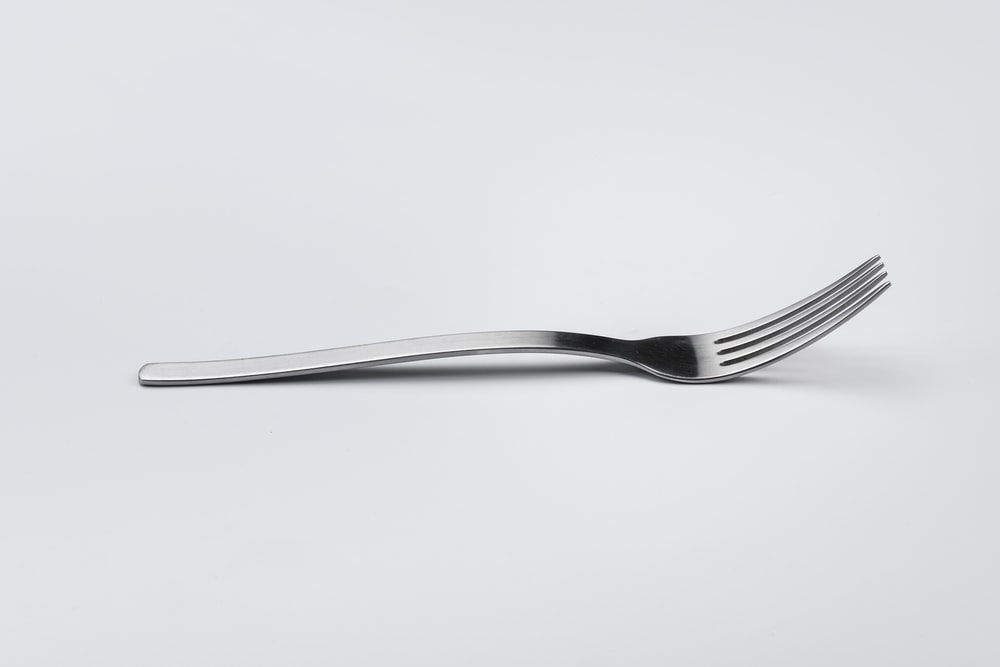 stainless steel fork on white surface