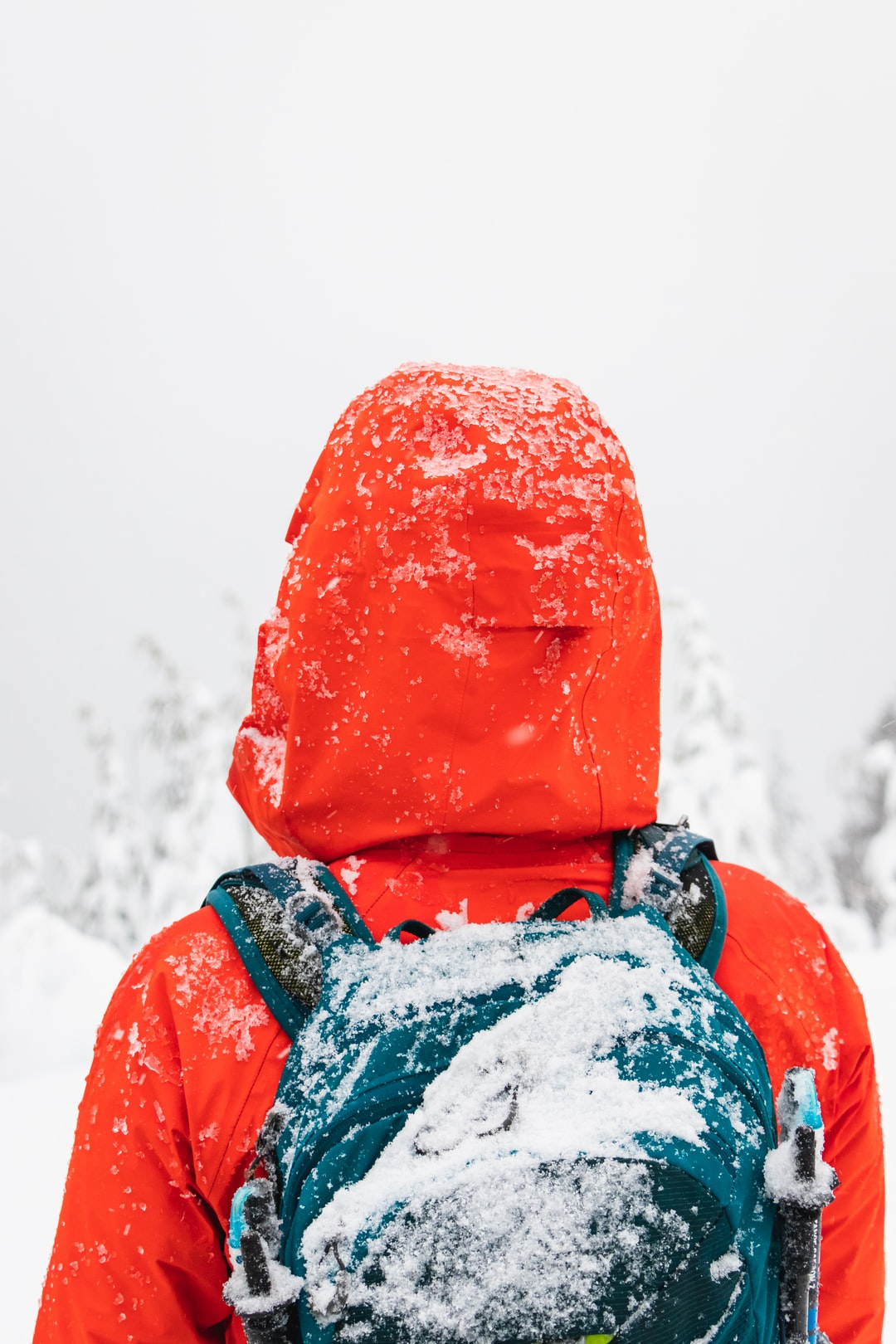 person wearing red winter jacket and backpack covered in snow