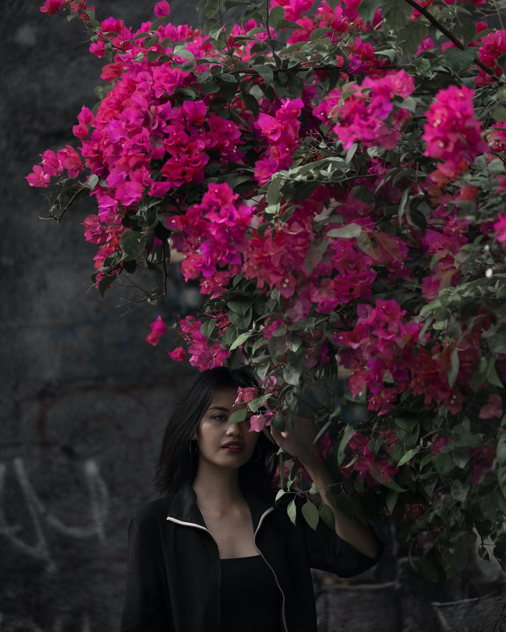 woman in black blazer holding pink flowers