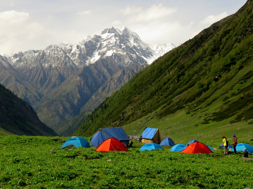 blue and red tent on green grass field near snow covered mountain during daytime