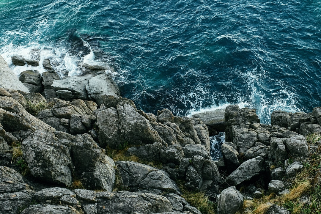 Beautiful blue sea with bright and lush waves hitting the cliffs. A heap of rocks by the sea.
