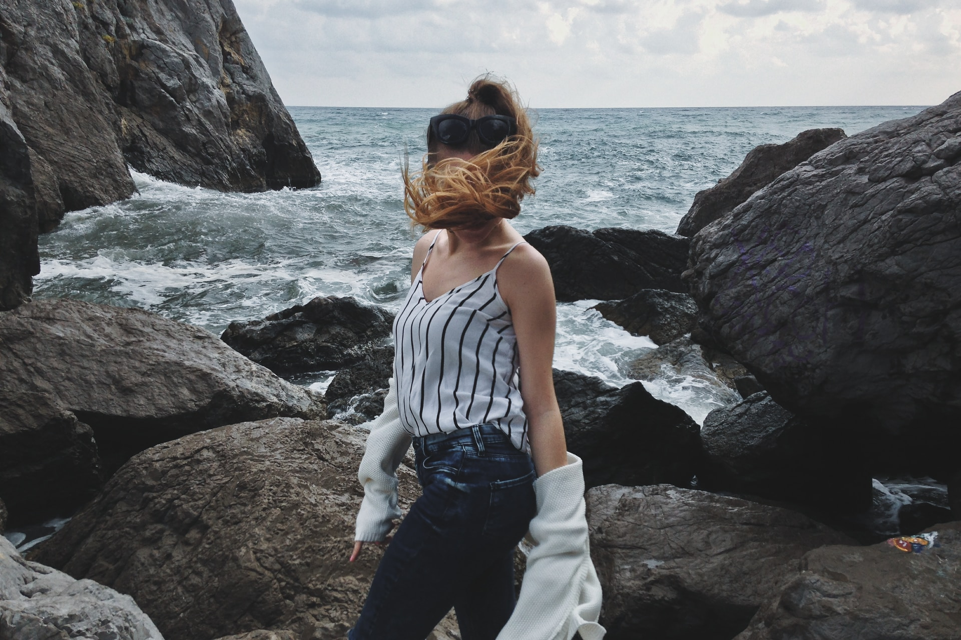woman in white tank top and blue denim jeans standing on rocky shore during daytime