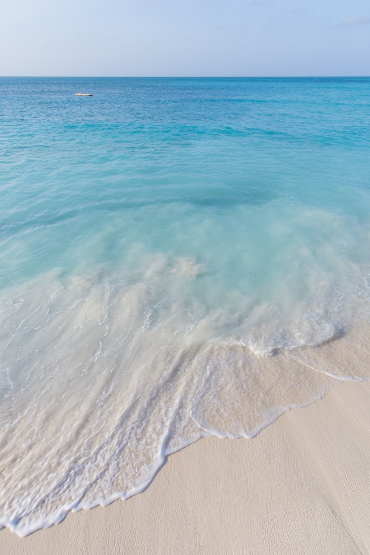 sea waves crashing on shore during daytime