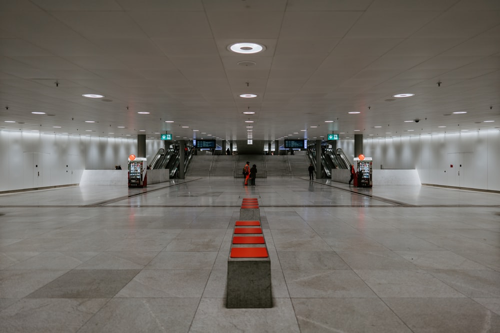 people walking on white floor tiles