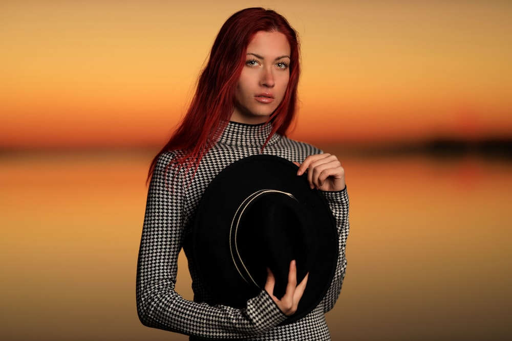 woman in black and white long sleeve shirt holding black hat