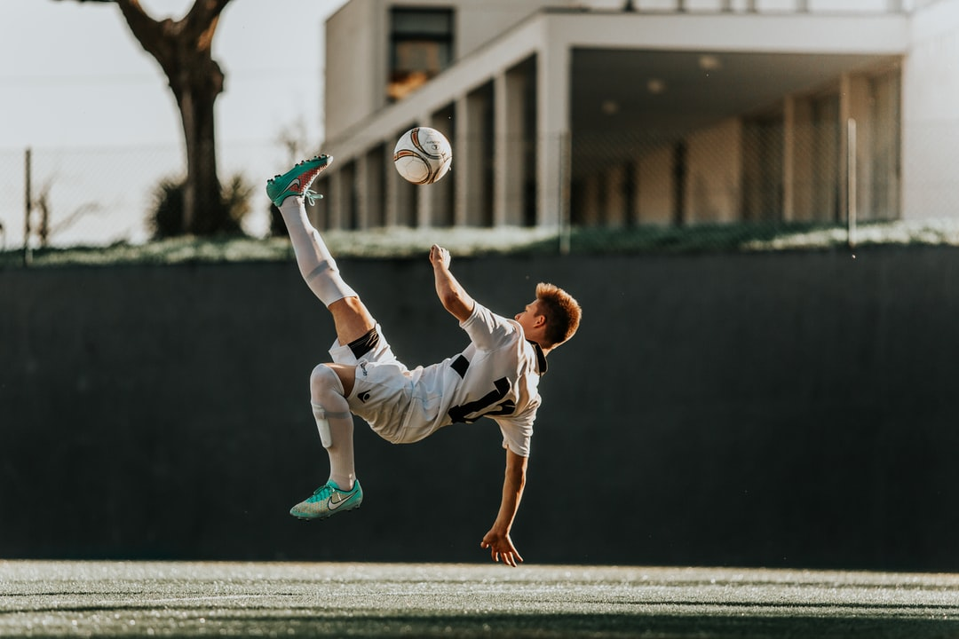 Man In White and Red Jersey Shirt and White Shorts Playing Soccer - unsplash