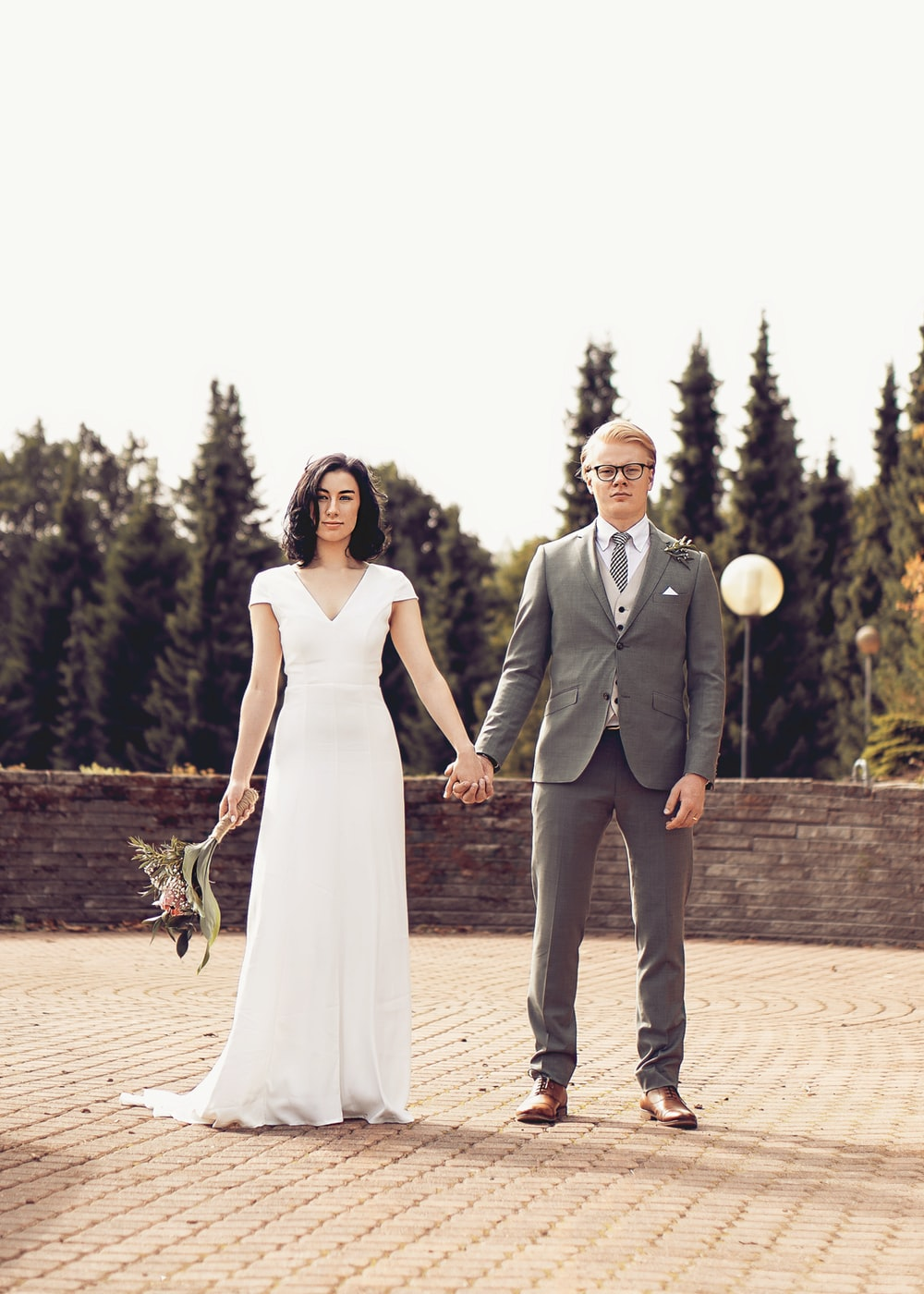 man in black suit and woman in white wedding dress standing on brown brick floor during