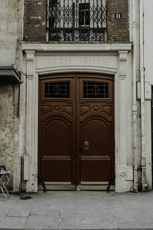 red wooden door on white concrete building