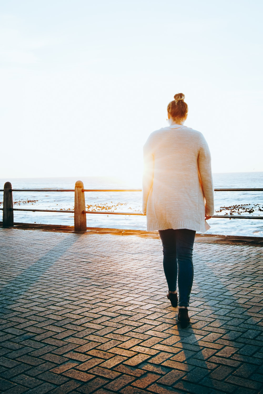 woman in white long sleeve shirt and black pants standing on dock during daytime