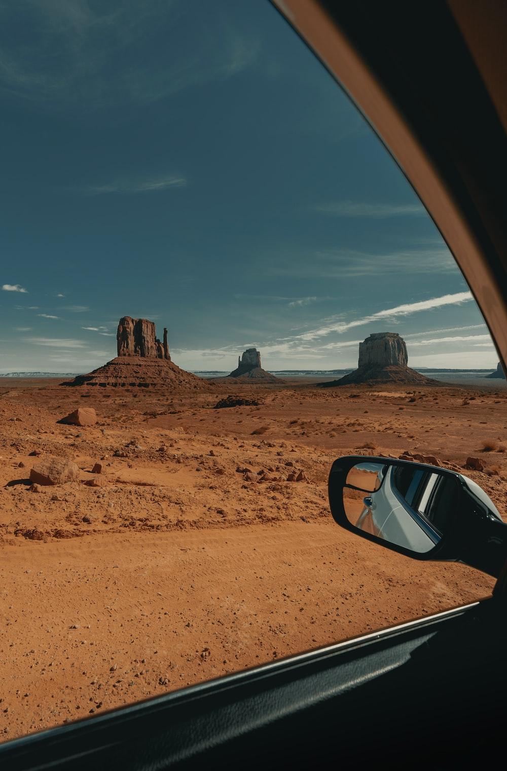 brown car on brown sand under blue sky during daytime