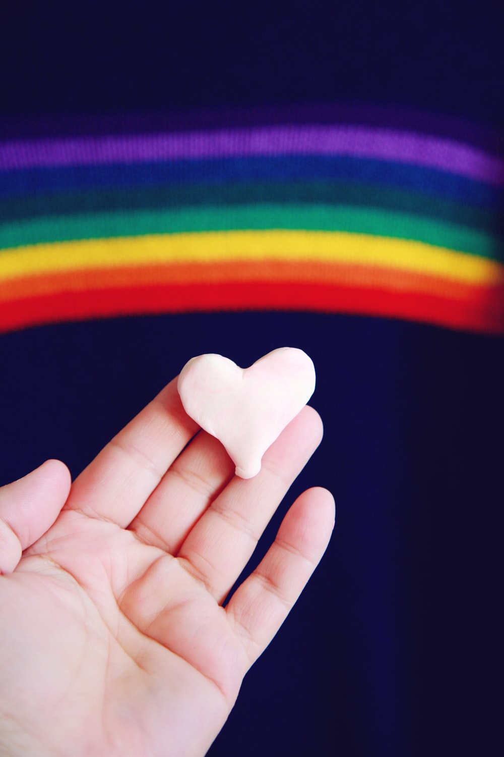 person holding white heart shaped ornament