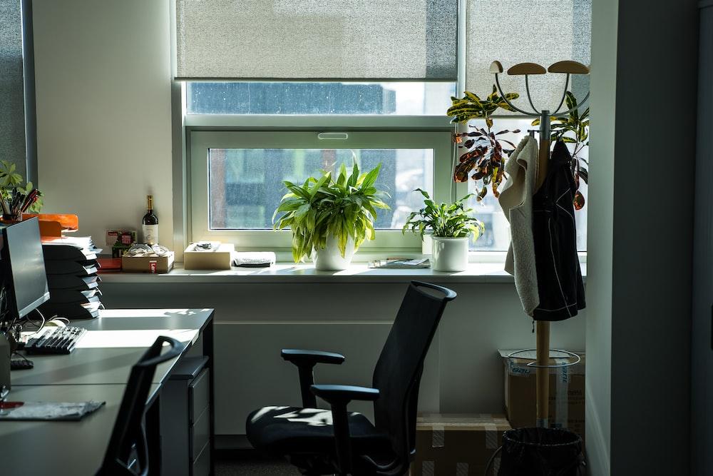 black office rolling chair beside white wooden desk