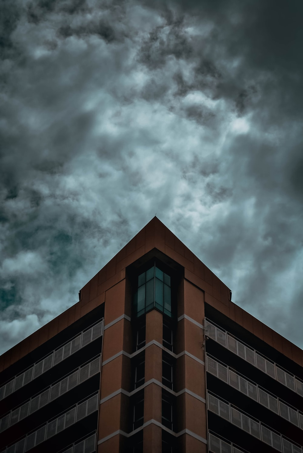 brown and black concrete building under gray clouds