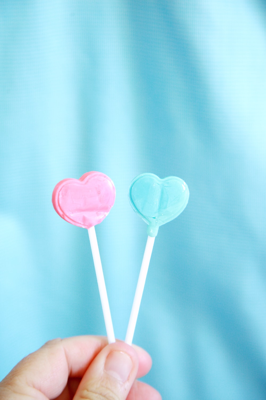pink heart lollipop on white textile