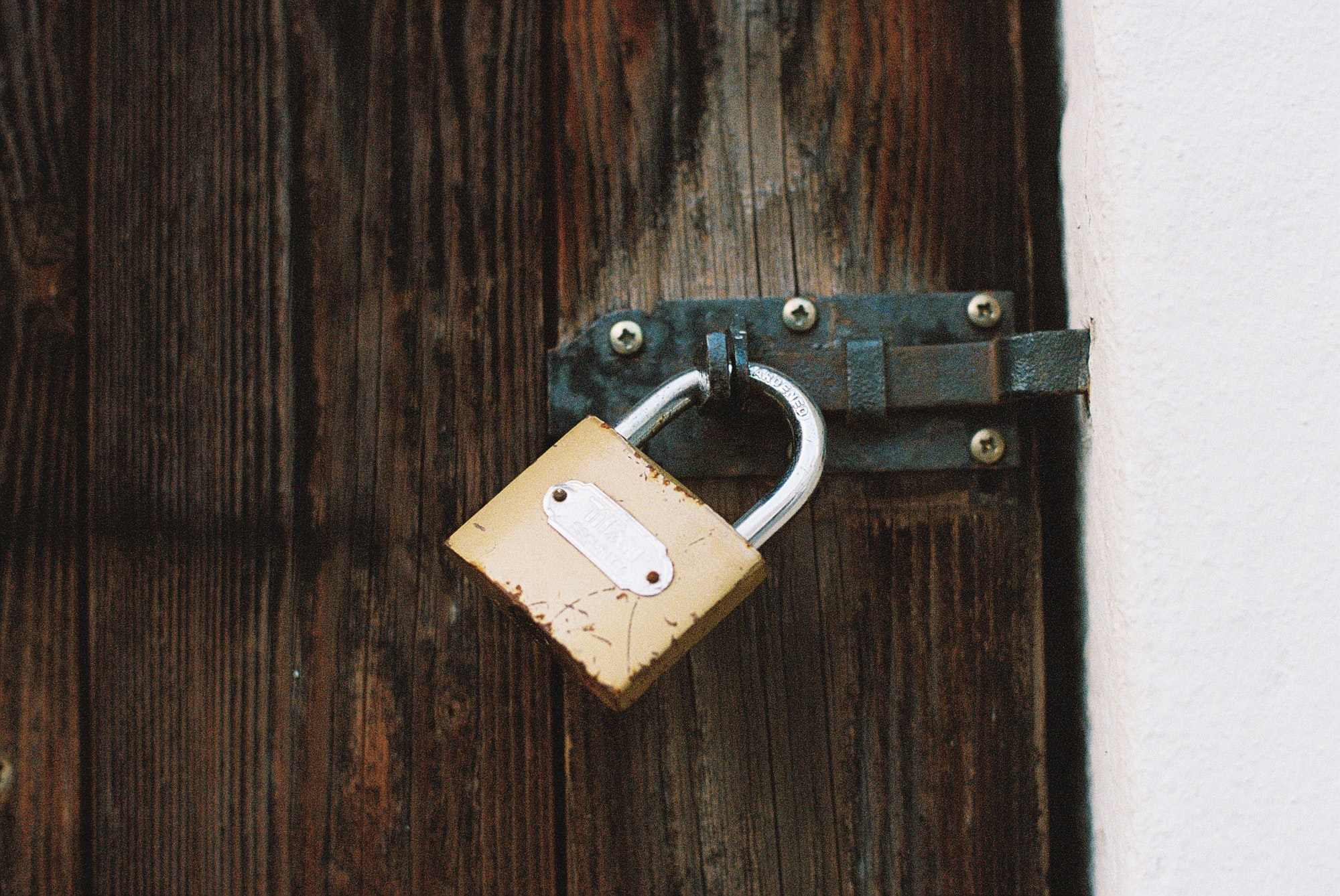 Locked padlock dark wooden weathered door. Made with Leica R7 (Year: 1994) and Leica Summilux-R 1.4 50mm (Year: 1983). Analog scan via nimmfilm.de: Fuji Frontier SP-3000. Film reel: Kodak Portra 800