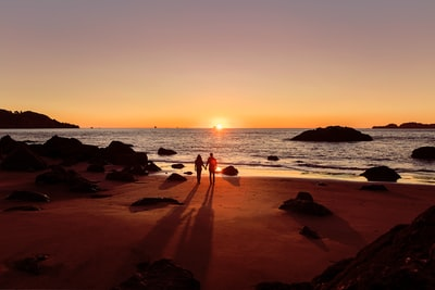 The Silhouette of a couple holding hands during sunset on Baker Beach in San Francisco.  Explore more at explorehuper.com