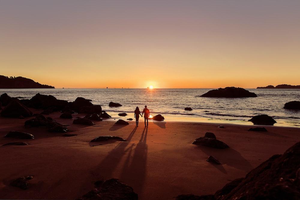 man in black shorts walking on beach during sunset
