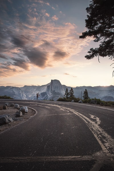 A couple standing the end of a long road during sunrise at Glacier Point in Yosemite National Park, California.  Explore more at explorehuper.com